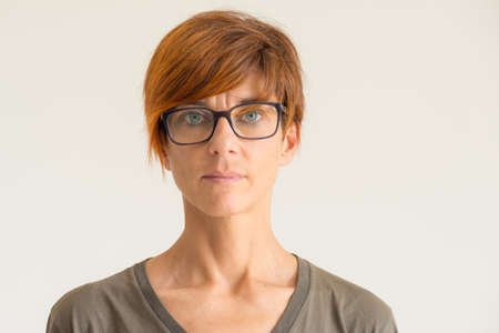 Waist up portrait of mature woman with red hairs, green eyes, eye glasses and serious facial expression, standing against the wall. Natural soft daylight, natural skin, neutral background. 免版税图像