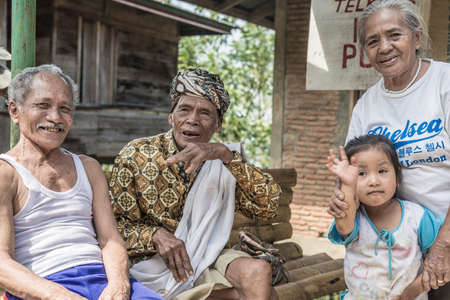 indonesia girl: Lokomata, Indonesia - September 6, 2014: Three wrinkled senior people of Toraja ethnicity, one in traditional attire, and a cute little girl having fun while looking at camera in Lokomata, Tana Toraja, South Sulawesi, Indonesia.