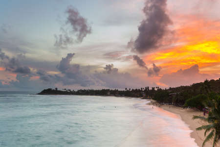 tourist resort: Golden sunset on desert beach with colorful sky and scenic cloudscape during monsoon time. Tourist resort in Unawatuna, Sri Lanka, famous travel destination. Blurred motion, long exposure.