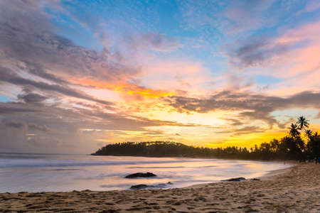 tourist resort: Golden sunset on desert beach with colorful sky and scenic cloudscape during monsoon time. Tourist resort in Mirissa, Sri Lanka, famous travel destination. Blurred motion, long exposure.