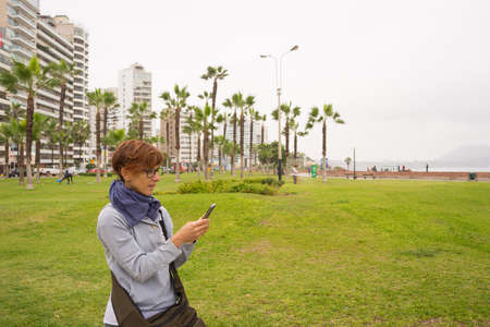 miraflores district: Female tourist using mobile smart phone while visiting Lima Miraflores. Concept of people sharing informations with new technology while traveling. Stock Photo