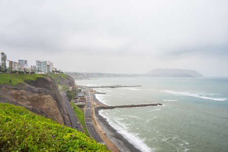 miraflores district: Dramatic coastline in Lima Miraflores viewed from above. Winter season, cloudy and foggy sky, waving ocean. Skyline in the background. Stock Photo