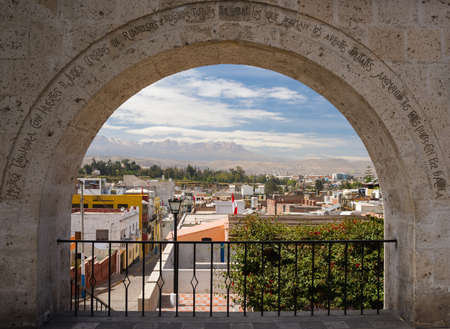 looking through frame: Volanic stone arch framing the city of Arequipa, famous travel destination and landmark in Peru, and the andean volcano range in the background.