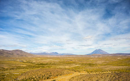 High altitude harsh barren landscape with scenic sky and volcanic cone in the distance. Wide angle view from above at 4000 m on the Andean highlands, Peru. Stock Photo