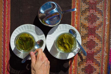 mate infusion: Tea cups with Coca leaves infusion known as Mate de Coca, typical drink of local people leaving at high altitude on the Andes in Peru and Bolivia. Shot directly above with natural daylight Stock Photo