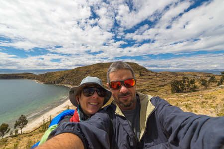 majestic: Adult european couple taking selfie in the majestic natural landscape of the Island of the Sun, Titicaca Lake, Bolivia. Concepts of people traveling around the world, wide angle view. Stock Photo