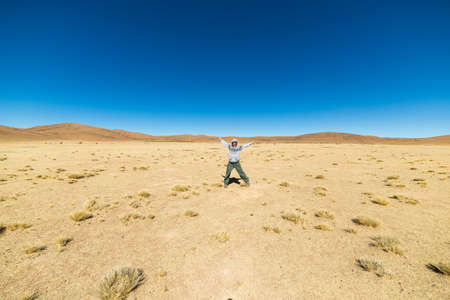 outstretched arms: Barren mountain range on the highlands of the Andes on the way to the famous Uyuni Salt Flat, among the most important travel destination in Bolivia. One person with outstretched arms, wide angle view. Stock Photo