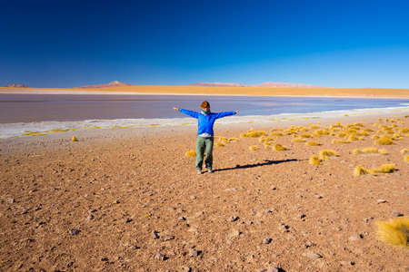 outstretched arms: One person with outstretched arms posing at Laguna Colorada (Multicolored Salty Lake) on the way to the famous Uyuni Salt Flat, among the most important travel destination in Bolivia. Wide angle view.