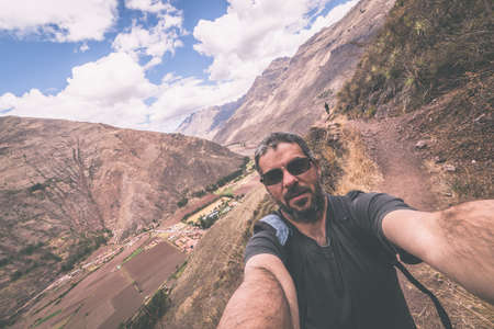 peru: Fellow traveler taking selfie while visiting Inca site of Pisac, Sacred Valley, major travel destination in Cusco region, Peru. Marsala toned image, wide angle view. Stock Photo