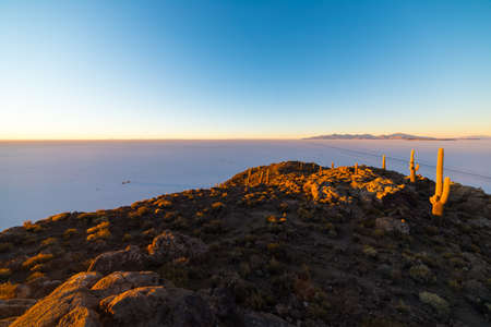incahuasi: Wide angle view of the Uyuni Salt Flat, among the most important travel destination in Bolivia. Shot taken at sunrise from the summit of the Incahuasi Island with glowing cactus. Stock Photo