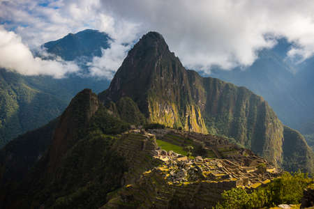 coming out: Machu Picchu illuminated by the first sunlight coming out from the opening clouds. The Incas city is the most visited travel destination in Peru.