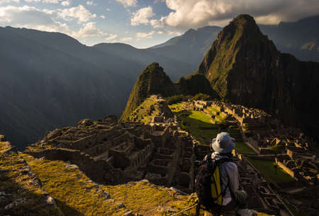 unesco culture heritage: Machu Picchu illuminated by the last sunlight. The Incas city is the most visited travel destination in Peru. One person sitting in contemplation.