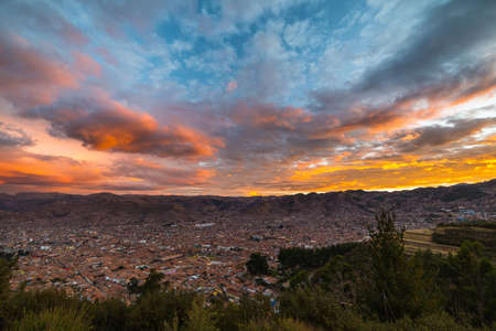 urban architecture: Panoramic view of Cusco town with glowing cloudscape and colorful sky at dusk. Cusco is among the most important travel destination in Peru and the entire South America.