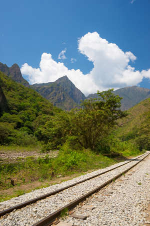urubamba valley: The railroad track crossing jungle and Urubamba river, connecting Machu Picchu village to hydroelectric station, mostly used for tourism and cargo purpose. Machu Picchu archeological site visible towards the top in the background.