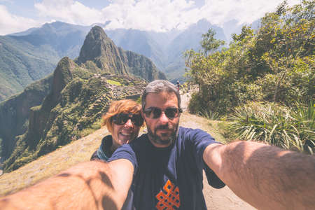 peruvian culture: Couple taking selfie on the terraces above Machu Picchu, the most visited travel destination in Peru. Adventures in South America, marsala toned image. Stock Photo