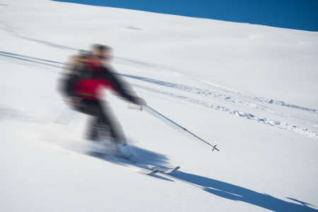 bardonecchia: One person skiing downhills off piste on snowy slope in the italian Alps, with bright sunny day of winter season. Thick Powder snow with ski tracks. Blurred motion.