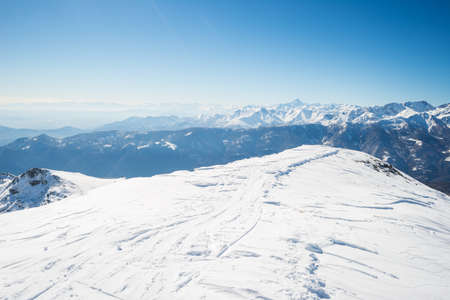 back country: Back country ski tracks on snowcapped ridge and summit with majestic view of the alpine arc in a winter scenery. Clear blue sky. Piedmont, italian Alps.