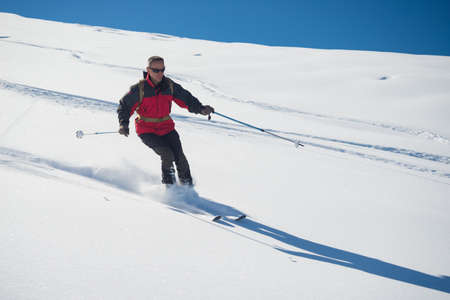 bardonecchia: One person skiing downhills off piste on snowy slope in the italian Alps, with bright sunny day of winter season. Thick Powder snow with ski tracks.