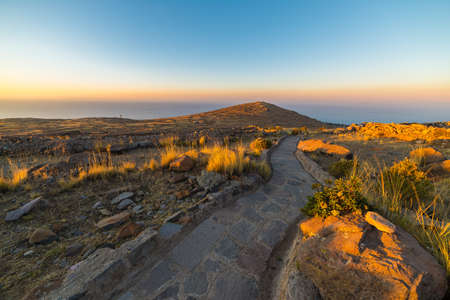 sinuous: Sinuous Inca trail at sunset on Amantani Island, Titicaca Lake, among the most scenic travel destination in Peru. Travel adventures and vacations in the Americas. Wide angle view with glowing terrain. Stock Photo