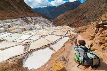 """Toeristen fotograferen witte zoutpannen ( """"Salineras de Maras"""") met een smartphone, een van de mooiste reisbestemming in Cusco Region, Peru. Het concept van het delen van reizen momenten met nieuwe technologieën. Stockfoto"""