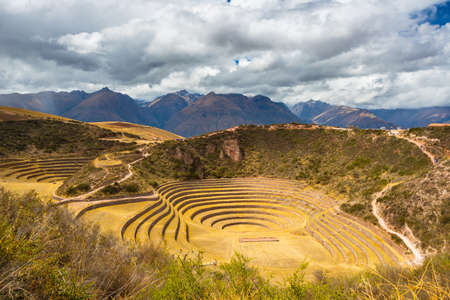 supposed: Wide angle view of the glowing majestic concentric terraces of Moray, supposed Incas laboratory in Sacred Valley, major travel destination in Cusco region, Peru. Dramatic cloudy sky. Editorial