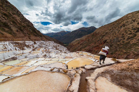 manual work: Worker carrying a big sack of salt, on the terraced salt pans in Maras, Urubamba Valley, Peru. Concept of manual work in developing countries. Wide angle image, rear view, unrecognizable person.