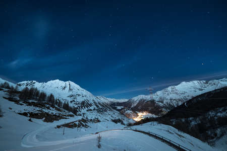 mountain valley: Aerial view of La Thuile village glowing in the night, famous ski resort in Aosta Valley, Italy. wonderful starry sky and majestic mountain landscape illuminated by the moon. Stock Photo