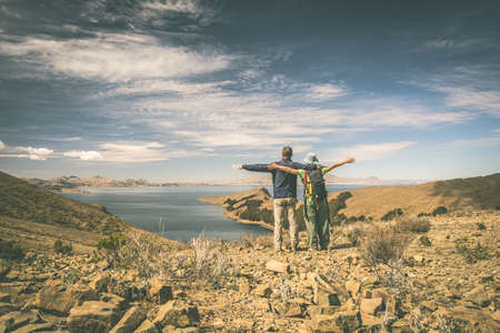 outstretched arms: Couple of tourist with outstretched arms looking at view on the Island of the Sun, Titicaca Lake, Bolivia. Concepts of people traveling around the world. Toned image, old retro look effect, rear view. Stock Photo