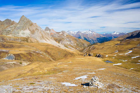 bardonecchia: Panoramic view of valley and mountain range in a colorful autumn with yellow meadows and high mountain peaks in the background. Wide angle shot in the Italian French Alps.