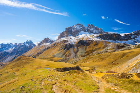 bardonecchia: Panoramic view of high mountain range in a colorful autumn with yellow meadows and snowcapped mountain peaks in the background. Wide angle shot in the Italian French Alps. Stock Photo