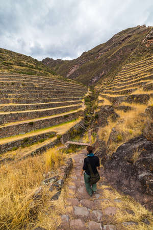 valley view: Tourist exploring the Inca Trails and the majestic terraces of Pisac, Sacred Valley, major travel destination in Cusco region, Peru. Vacations and adventures in South America.
