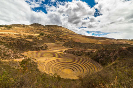 supposed: Wide angle view of the glowing majestic concentric terraces of Moray, supposed Incas laboratory in Sacred Valley, major travel destination in Cusco region, Peru. Dramatic cloudy sky. Stock Photo