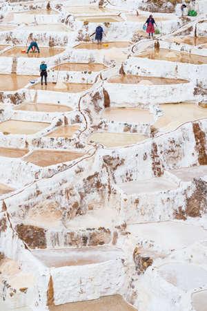 sal: Maras, Per� - 5 de septiembre de 2015: Los trabajadores, la mayor�a mujeres y ni�as, manualmente extrayendo minerales de salinas en terrazas en Maras, Valle del Urubamba, Per�. Concepto de trabajo manual en los pa�ses en desarrollo.