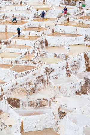 manual work: Maras, Peru - September 5, 2015: Workers, mostly women and girls, manually extracting minerals from terraced salt pans in Maras, Urubamba Valley, Peru. Concept of manual work in developing countries. Editorial