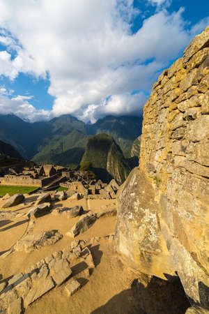 urubamba valley: Machu Picchu stone wall details and ruins illuminated by the last sunlight. Wide angle view above over the majestic Urubamba Valley with dramatic sky.