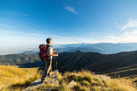 conquering: Hiker relaxing on the mountain summit at sunset and looking at majestic panorama of the italian Alps in autumn season. Wide angle view. Concept of conquering the success and healthy lifestyle.