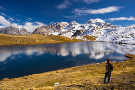bardonecchia: Hiker looking the outstanding view of high altitude blue lake and majestic snowcapped mountain peak in autumn season. Wide angle shot in the Italian French Alps. Stock Photo