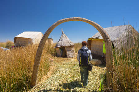 peru: Tourist roaming in a village of the Uros Islands, entirely made of Totora Reeds, floating on Titicaca Lake, among the most interesting travel destination in Peru. Travel adventures and vacations in the Americas. Stock Photo