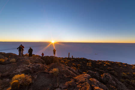 incahuasi: Group of tourists watching the rising sun at the horizon over the majestic Uyuni Salt Flat, among the most important travel destination in Bolivia. Wide angle shot from the summit of the Incahuasi Island with glowing rocks and unrecognizable people.
