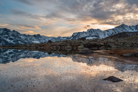 asl: High altitude alpine lake in idyllic land once covered by glaciers. Reflection of snowcapped mountain range and scenic colorful sky at sunset. Wide angle shot taken on the Italian Alps at 2200 m asl.