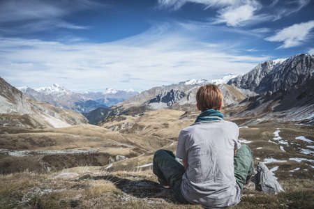 One person sitting on the mountain summit and looking at wide panorama of the valley below and high mountain range of the Italian French Alps. Rear view, toned image, crispy effect, vignetting added.