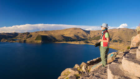 mujer mirando el horizonte: Female tourist looking at the majestic panoramic view from the top of the mountain in Copacabana, Titicaca Lake, among the most scenic travel destination in Bolivia. Travel adventures and vacations in the Americas. Foto de archivo