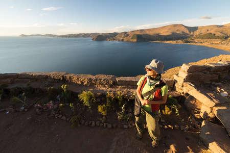 mujer mirando el horizonte: Turista femenino mirando la vista panorámica majestuosa puesta de sol desde la cima de la montaña en Copacabana, Lago Titicaca, entre el destino de viaje más pintoresco en Bolivia. Las personas que viajan en las Américas. Foto de archivo