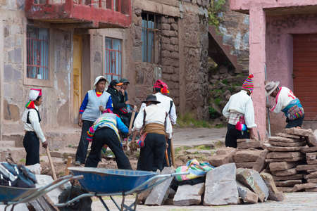 peruvian ethnicity: Taquile, Peru - September 1, 2015: Community of traditionally dressed people in Taquile Island, Titicaca Lake, Peru. About 2200 people live on the island. They speak Quechua language.