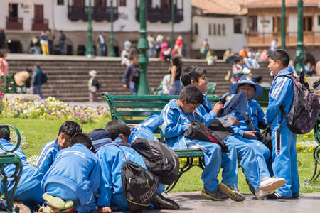 plaza de armas: Cusco, Peru - September 3, 2015: Group of school children in blue uniform playing in Plaza de Armas, Cusco, Peru.