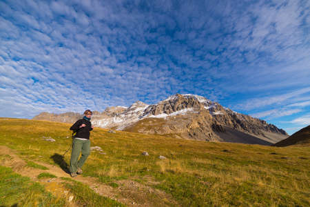 bardonecchia: Female hiker walking on footpath in a colorful valley with scenic sky and clouds. Wide angle shot from below in the Italian French Alps. Concept of healthy lifestyle.