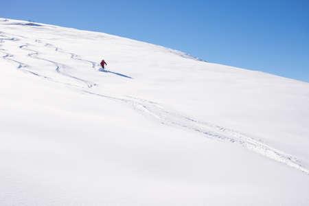Een persoon skiën off-piste afdalingen op besneeuwde helling in de Italiaanse Alpen, met heldere zonnige dag van de winter seizoen. Dikke Poeder sneeuw met skipistes. Stockfoto