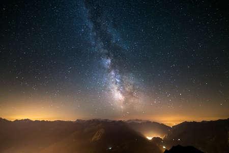 De uitzonderlijke schoonheid van de Melkweg en de sterrenhemel vastgelegd op grote hoogte in de zomer op de Italiaanse Franse Alpen met gloeiende Aostadal hieronder. Groothoek bekijken, wat aanvaardbaar digitale ruis en graan als gevolg van lange blootstelling en hoge iso Setti Stockfoto