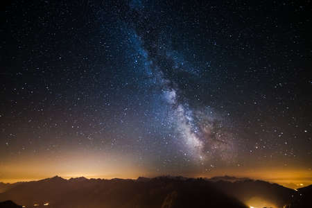 acceptable: The outstanding beauty of the Milky Way and the starry sky captured at high altitude in summertime on the italian french Alps with glowing Aosta Valley below. Wide angle view, some acceptable digital noise and grain due to long exposure and high iso setti Stock Photo