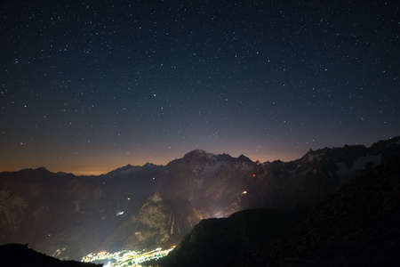skyway: Stunning night view of Mont Blanc peak (4810 m) with breathtaking starry sky above and the glowing cable car up to P. Helbronner. Wide angle view from 3000 m. Stock Photo